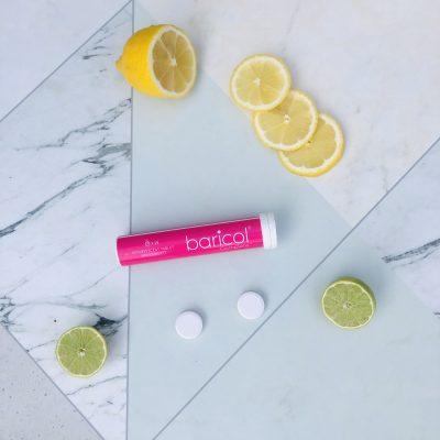 Baricol rosa rör med brustabletter på marmorbord omgiven av citrusfrukter