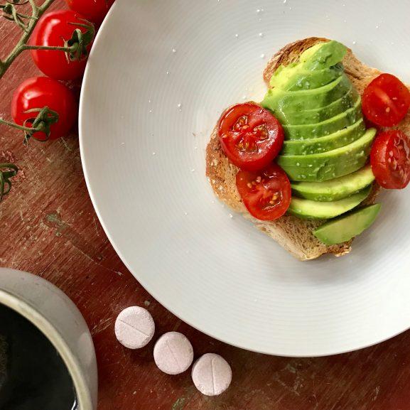tre Baricol tuggtabletter till frukost kaffe och avocadosmörgås med tomat