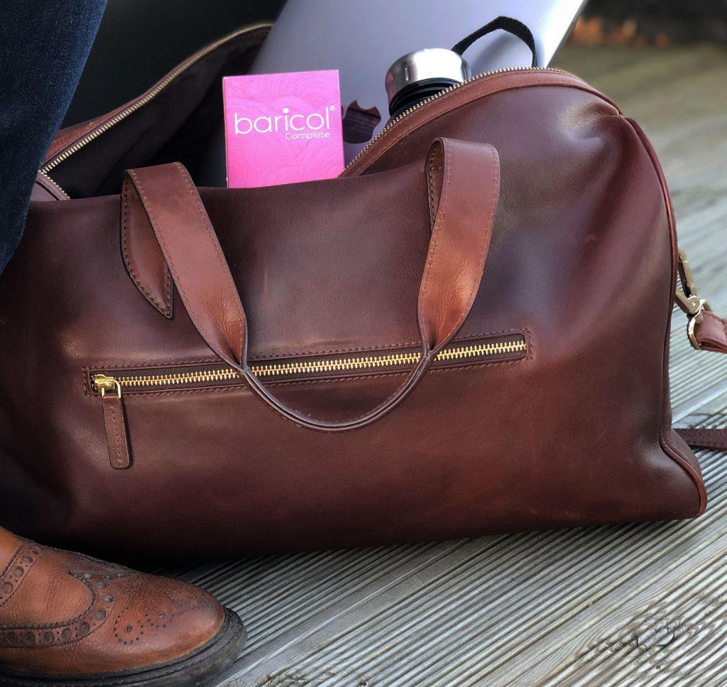 Brun skinnväska står bredvid skinnsko i viskan sticker rosa baricol ask upp
