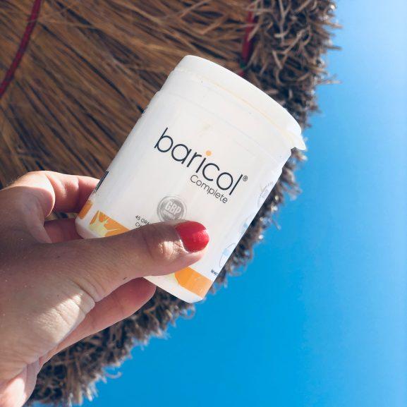 Hand håller baricol complete tuggtablett ask mot blå himmel och stråparasoll