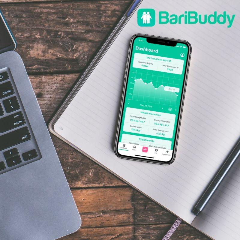 BariBuddy appen för viktopererade på svart telefon ligger på block på ett träbord