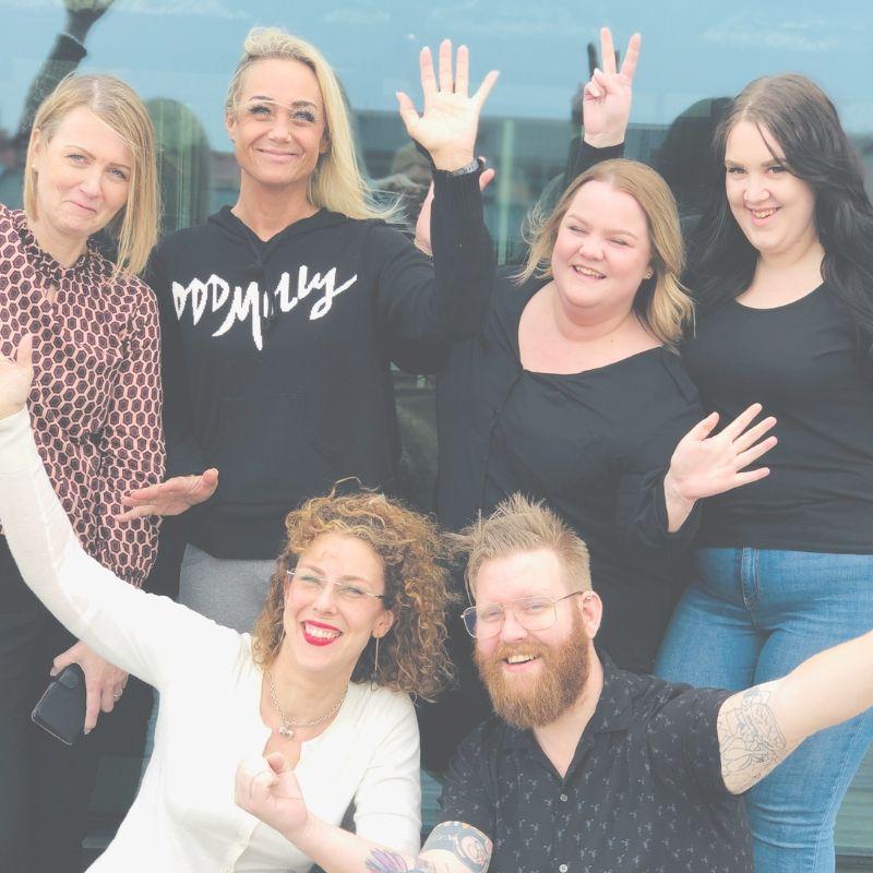 Bild på 5 tjejer och en kille som sträcker upp händerna mot luften
