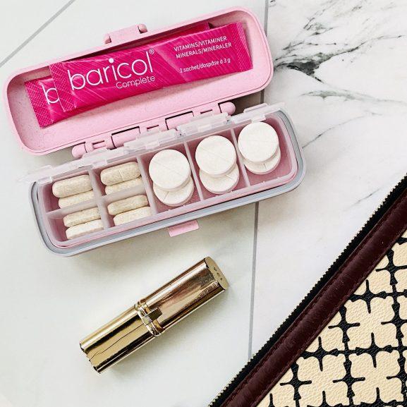 baricol rosa vitamindosett fylld med vitaminer omgiven av handväska och läppstift