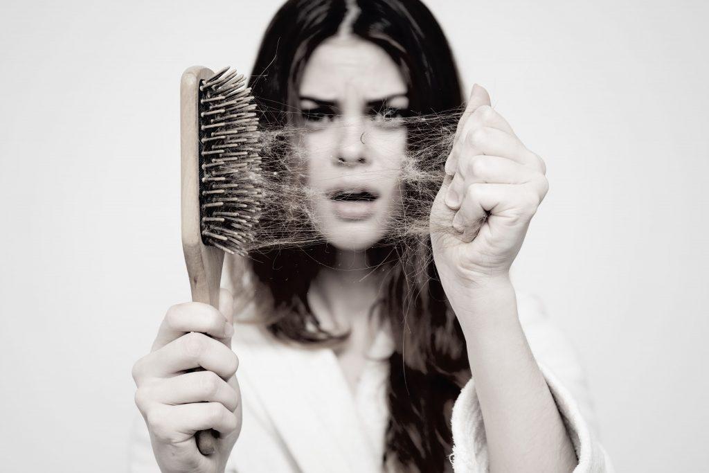 håravfall, kvinna med hårdborste framför sig fylld med hår